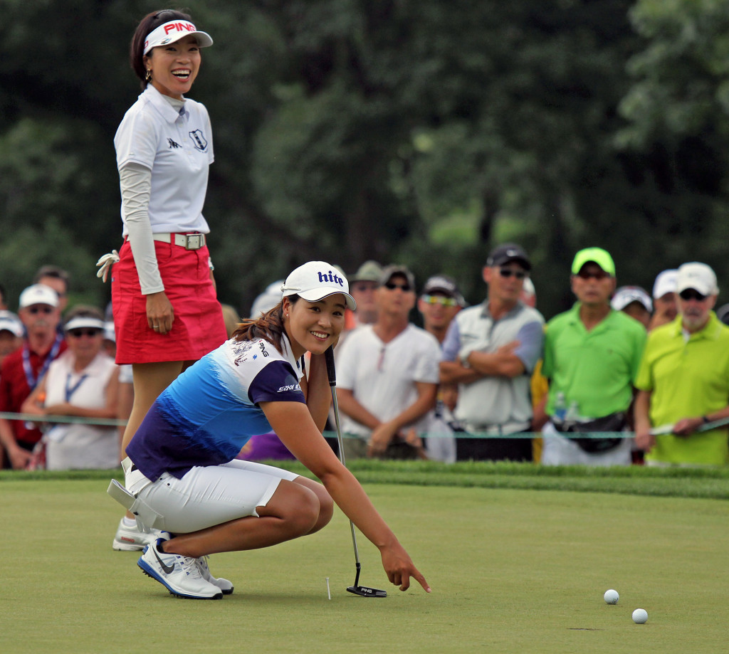 In Gee Chun, kneeling, looks to the crowd for ball placement after Shiho Oyama's ball hit hers and moved it on the 1st hole, during final day action of the 70th US Women's Open at Lancaster Country Club Sunday July 12, 2015. (Photo/Chris Knight)